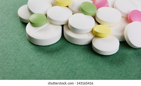 Pills and tablets on a green background