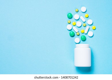 Pills, tablets and vitamin on blue background top view. Medical pharmacy concept.