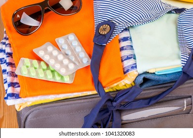 pills that need to be taken on a trip lie in a suitcase near with other things