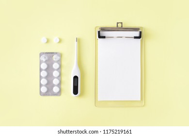 Pills, thermometer and note for doctor prescription on yellow background. Cold and flu treatment set. Flat lay, top view.