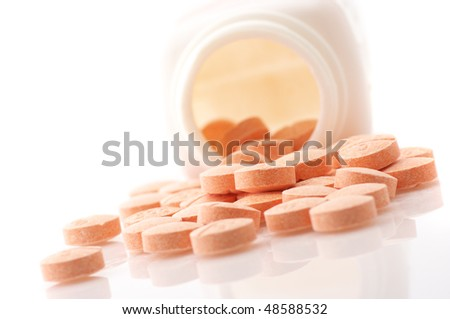 Pills of vitamin C spilled out open container on white background.