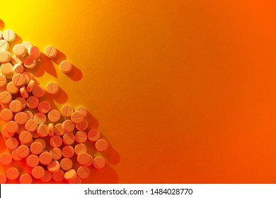 Pills and vitamins on orange neon background. Frame of pills. Copy space.