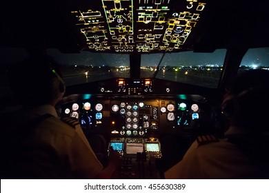 Pilot in airplane cockpit night