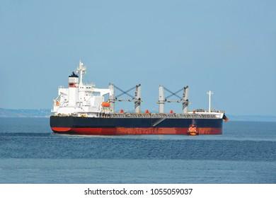 Pilot assisting bulk cargo ship to harbor quayside