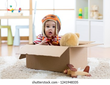 Pilot aviator baby boy with teddy bear toy and planes plays in cardboard box