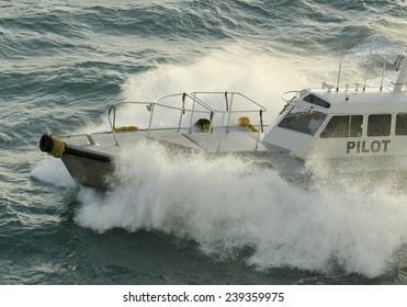Pilot boat crashing through a wave