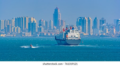 Pilot boat delivers a harbor pilot to container cargo ship in front of Jiaozhou Bay shore, Qingdao, China .