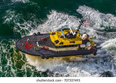 A pilot boat escorting a cruise line out of nova scotia or Canada.