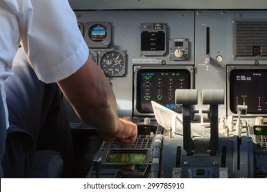 A pilot checking instruments in a plane cockpit