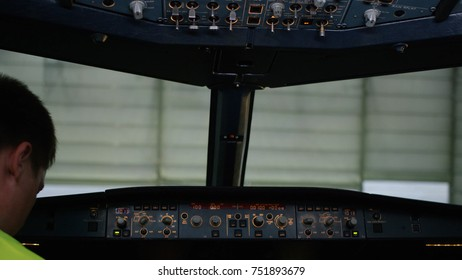 A pilot checking instruments in a plane cockpit. Rear view of pilot operating controls of corporate jet. the pilot checks all the systems. Rear view of pilot and copilot operating controls of