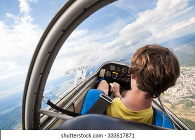 Pilot in cockpit of an aircraft which flies over landscape, Flying glider with pilot, Lightweight glider flying just above ground