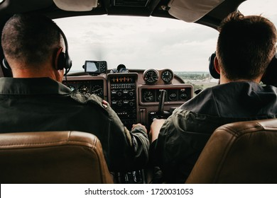 Pilot and cockpit. Aircraft Pilot at work. Rear view of pilots. A man flying in a helicopter, with his sopilot looking outside the plane.