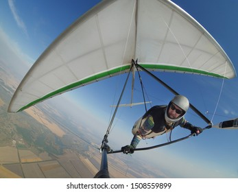 Pilot controls his hang glider wing on hign altitude. Extreme sport action shot