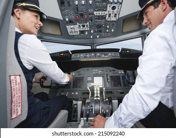 Pilot and co-pilot driving airplane in cockpit smiling