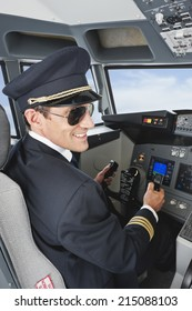 Pilot driving airplane in cockpit smiling
