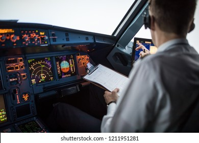 Pilot executing pre-flight procedures in a commercial airliner cockpit before takeoff