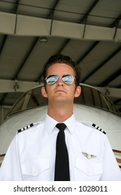 Pilot in front of his airplane in the hangar - notice the sky reflection in his shades