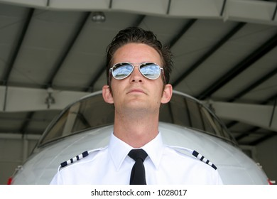Pilot in front of his business jet in the hangar - notice reflection in shades