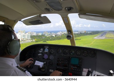 Pilot is getting ready for landing overlooking the city, ocean, beach and landing strip on the background.