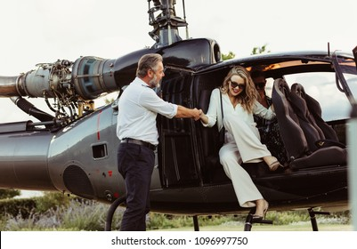 Pilot holding hand of a woman getting off the helicopter. Wealthy young woman traveling by her helicopter.