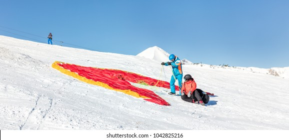 The pilot prepares the paraglider for the flight from the slope of Todorka - Bansko resort, Bulgaria