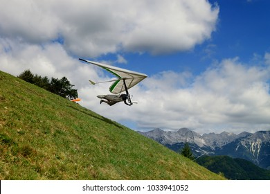 Pilot runs with a hang glider on a green grassy slope high in the mountains with blue sky and clouds above