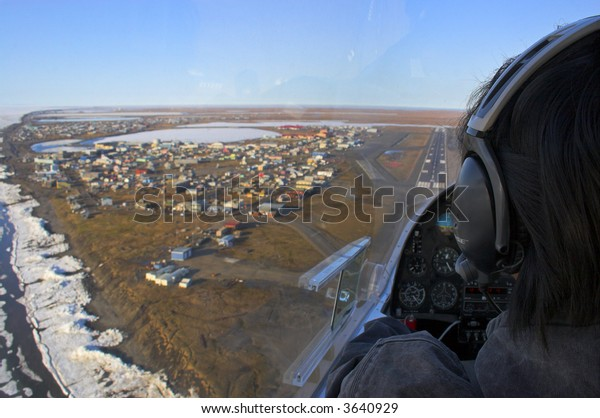 Pilot of a small airplane flies over Arctic Ocean shore and is getting ready to land on the airstrip of the whaling village of Barrow, the north most point of the USA