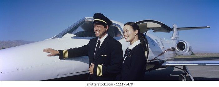 Pilot standing with stewardess in front of an aircraft
