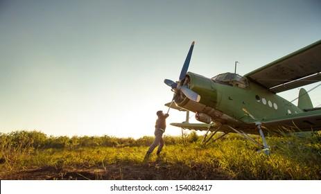 Pilot is starting engine of vintage plane. Rural background.