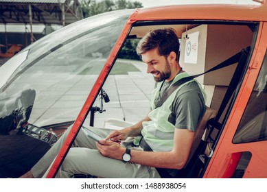 Pilot with tablet. Bearded pilot wearing bright vest holding little tablet while sitting in private helicopter