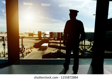 Pilot in uniform standing at boarding gate area in airport terminal, is looking out of window to see ground staff preparing an airplane to be ready for his flight. Seen from the back in evening sunset