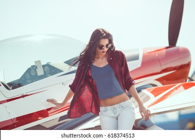 Pilot woman standing at cabin plane outdoors in sunny day. Attractive young multi-racial Asian Caucasian sexy girl in jeans and shirt near wing sport airplane in airport.