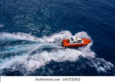 Pilots boat aerial view sailing in blue ocean sea with foam wake