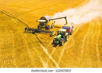 PILSEN, CZECH REPUBLIC - JULY 1, 2018: Aerial view of harvest. Combine harvester and tractor harvesting wheat field. Agriculture from drone view.