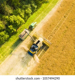 PILSEN, CZECH REPUBLIC - JULY 18, 2017: Aerial view of summer harvest. Combine harvester and tractor harvesting field. Agriculture from drone view.