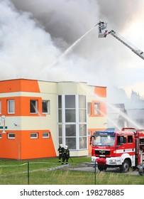 PILSEN, CZECH REPUBLIC - JUNE 12 2014: unidentified professional firefighters extinguishing burning factory. Fire department of Pilsen City.