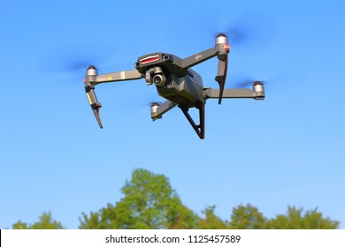 PILSEN, CZECH REPUBLIC - MAY 18, 2018: DJI Mavic Pro drone flying over trees. Quadcopter with predator nose art. Modern drone with obstacle avoidance sensors and 4K camera.