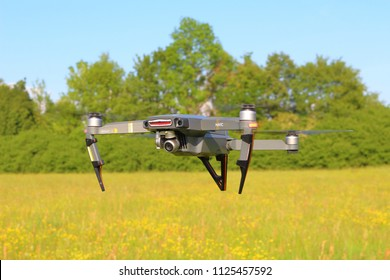 PILSEN, CZECH REPUBLIC - MAY 18, 2018: DJI Mavic Pro drone flying over flowering meadow. Quadcopter with predator nose art. Modern drone with obstacle avoidance sensors and 4K camera.