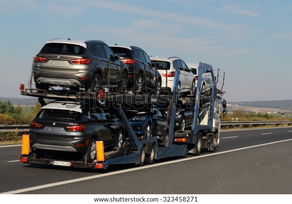 PILSEN, CZECH REPUBLIC - OCTOBER 2, 2015: Truck carrying new BMW cars on the D5 highway. The D5 is important transport connection between West Bohemia and Bavaria in Germany.