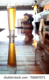 A pilsner beer on the counter of a bar.