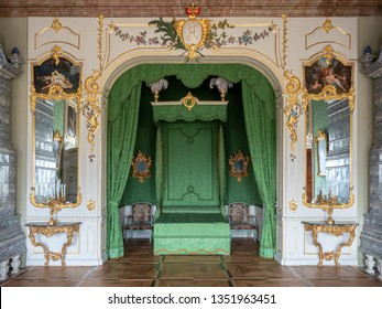 PILSRUNDALE, LATVIA, March 24, 2019: Interior of Rundale palace - The Duke's Bedroom. The parquet floor, ceiling painting, green walls.