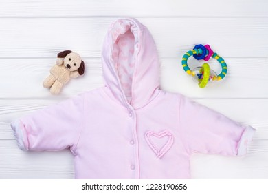 Pin baby jumpsuit and toys. Girl fleece coveral, plush dog and rattle.