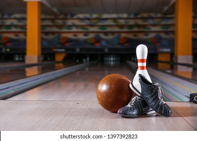 Pin, ball and shoes on floor in bowling club