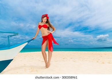 Pin up beautiful young woman in red bikini on a tropical beach.