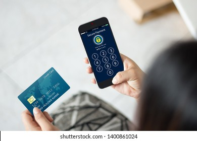 Pin code Password,Secure payment concept.Female hands holidng credit card and using mobile phone