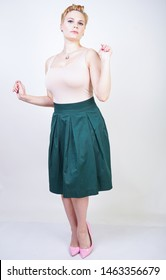 Pin up curvy girl in green pleated midi skirt on white