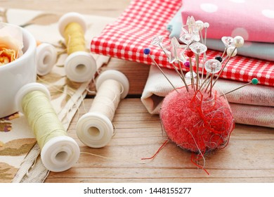 Pin cushion with sewing pins, colorful fabrics in the background.
