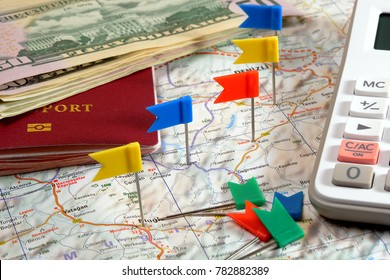 pin flags marking  travel itinerary points on map and passport, dollar banknotes and calculator