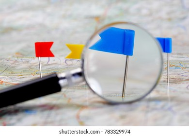 pin flags marking  travel itinerary points on map and magnifying glass in background