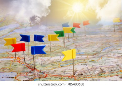 pin flags marking travel itinerary points on map against background of sun shining on cloudy sky, collage, travel concept